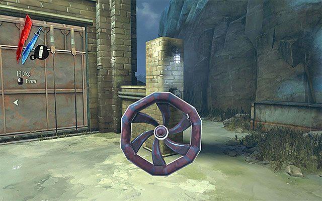 Do niedostępnego pomieszczenia wspomnianego wyżej ostatniego budynku możesz z kolei przedostać się od strony dachu (zeskoczenie na niewielki balkonik i zniszczenie drewnianych belek blokujących przejścia) lub odnajdując w warsztacie duże pokrętło i przenosząc je do odpowiedniego slotu (powyższy scre - Zbadanie podwórza - Misja 2 - High Overseer Campbell - Dishonored - poradnik do gry