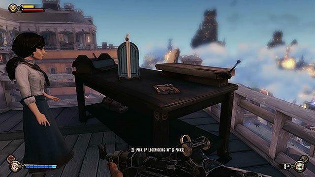 Zaraz za schodami znajdziesz stolik, na którym leży zestaw 2 wytrychów oraz Ekwipunek #11 - Głowa - Uruchom gondolę na Żołnierskim Polu - Rozdział 12 - Wróć na Plac Sali Bohaterów - BioShock: Infinite - poradnik do gry
