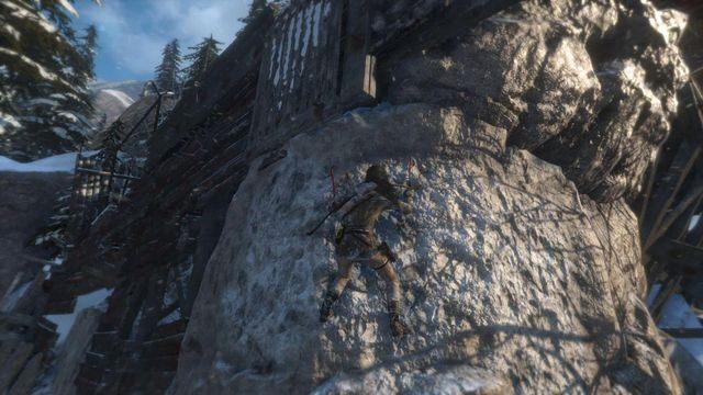 Przejdź po wąskim fragmencie rusztowania i skocz w kierunku skalnej ściany nie zapominając, aby wbić w nią czekan - Dotrzyj do wejścia do kopalni   Znów sama - Rise of the Tomb Raider - poradnik do gry