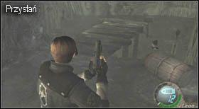 Koło wrót, z których właśnie wyszedłeś, zamontowana jest lampa, a do niej przyczepiono klejnot - Village (2-1) - przystań i boss - Resident Evil 4 - PC - poradnik do gry